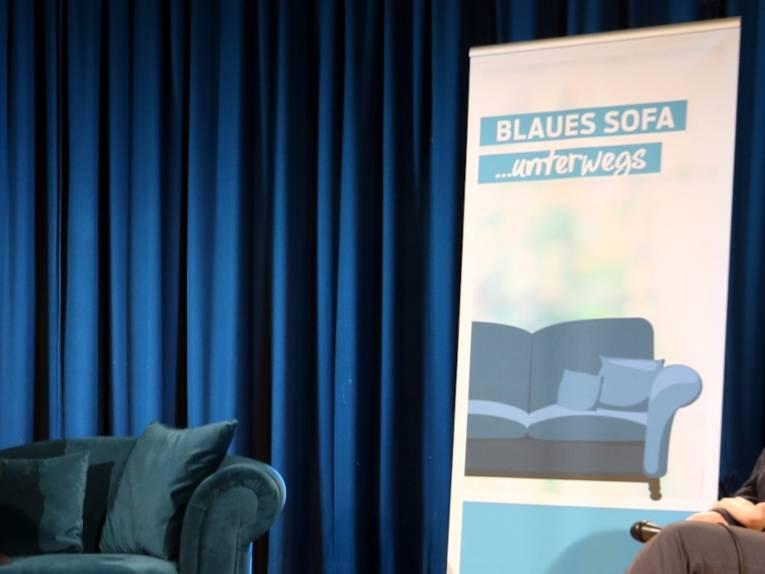 """Ein blaues Sofa steht vor einem blauen Vorhang, rechts daneben steht ein Rollup-Display auf dem steht """"BLAUES SOFA ...unterwegs""""."""