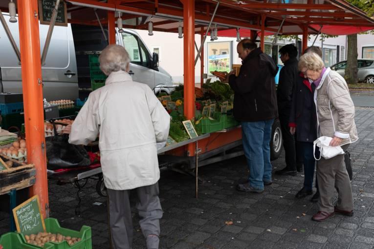 Kund*innen an einem Stand auf dem Wochenmarkt Rübezahlplatz