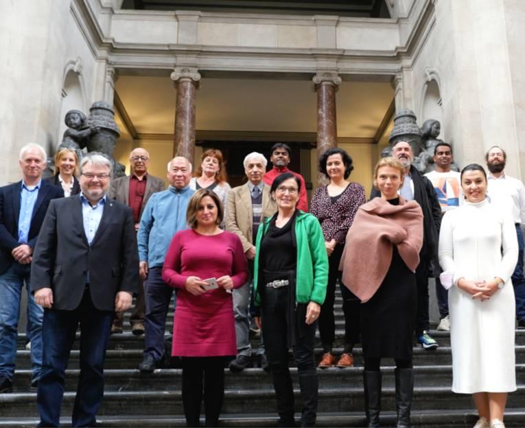 16 Menschen, neun Männer und sieben Frauen, stehen auf der Treppe im Neuen Rathaus und schauen in die Kamera. Es sind Mitglieder des Internationalen Ausschusses und vom WIR 2.0-Projektteam.