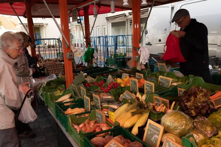 Kund*innen kaufen an einem Obst- und Gemüsestand Waren ein.
