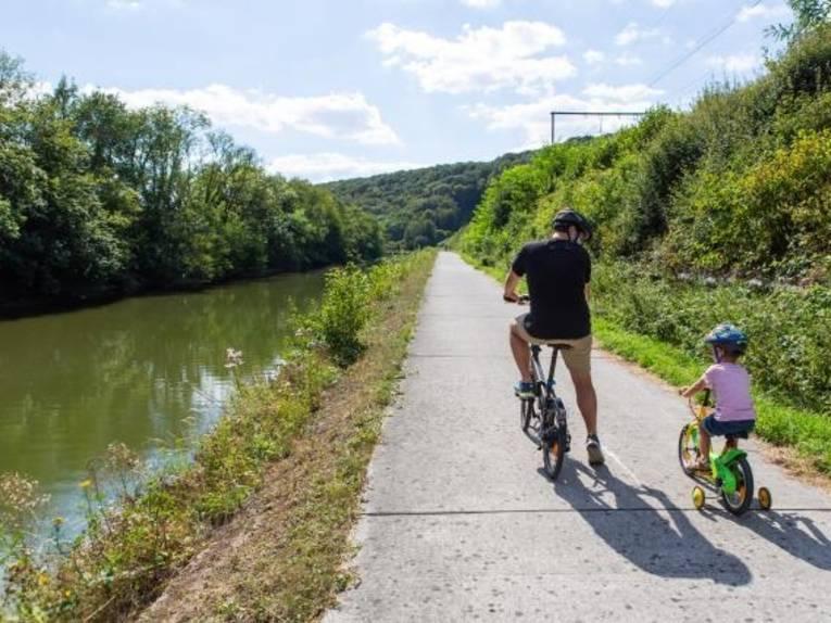 Mann auf Fahrrad und Kind auf Dreirad an einem Kanal