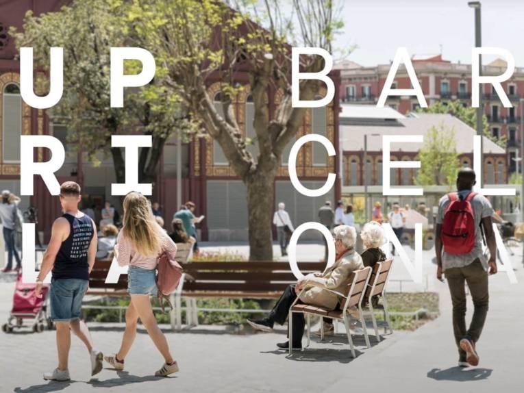 Szene aus einem Video. Zu sehen sind mehrere Menschen in einem urbanen Gebiet. Mittendrin Bänke und Bäume.