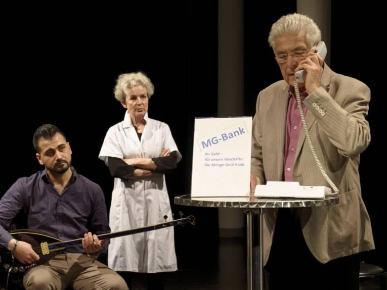 Szenefoto des Theaterstücks: 3 Schauspieler, einer als Bankberater am Telefon, ein Mensch mit Gittare und eine Frau mit Kittel