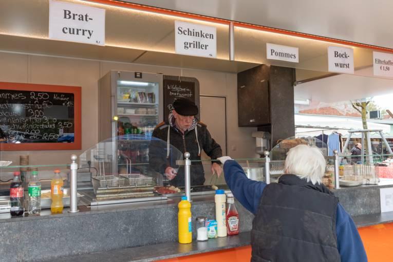 Eine Kundin kauft Bratwurst an einem Stand.