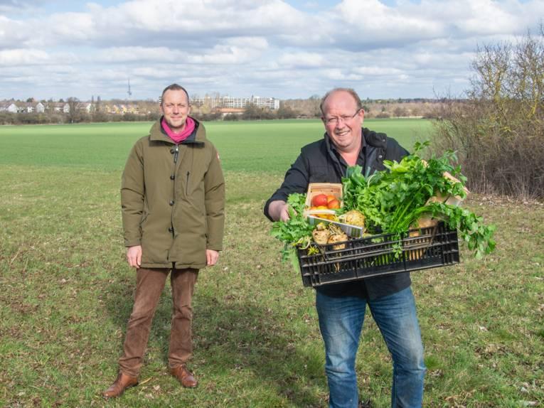Zwei Männer auf einem Acker. Eine hält eine Kiste mit Gemüse.