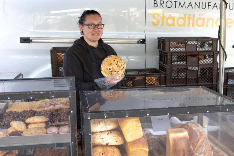 Eine Verkäuferin hält ein frisch gebackenes Brot in die Kamera.