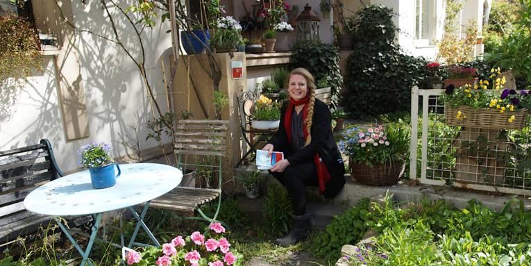Eine lächelnde Frau in einem Garten.