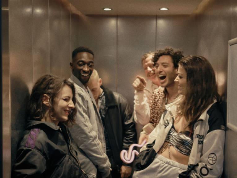 Das Foto zeigt Babtou und seine freunde die in einem Fahrstuhl sind und miteinander lachen.