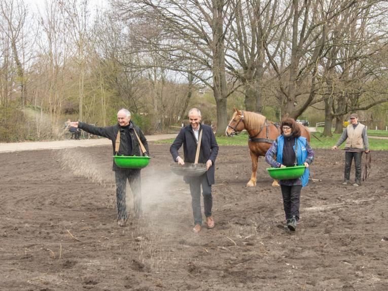 Drei Personen auf einer umgegrabenen Fläche. Sie streuen Saaten. Im Hintergrund ein Pferd, das von einer weiteren Person geführt wird.