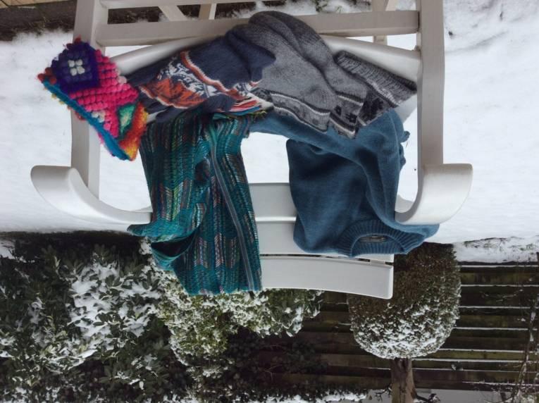 Strickpulli, Handschuhe, Socken, Schal und Strinband auf einem Stuhl in winterlicher Umgebung.