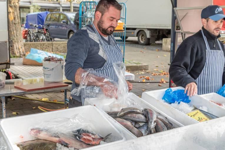 Zwei Fischverkäufer an einem Marktstand.