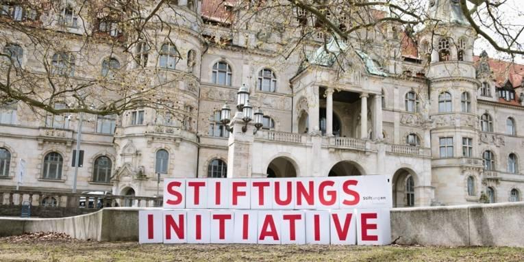 Kartons mit Buchstaben, die das Wort Stiftungsinitiative ergeben, vor einem historischen Gebäude