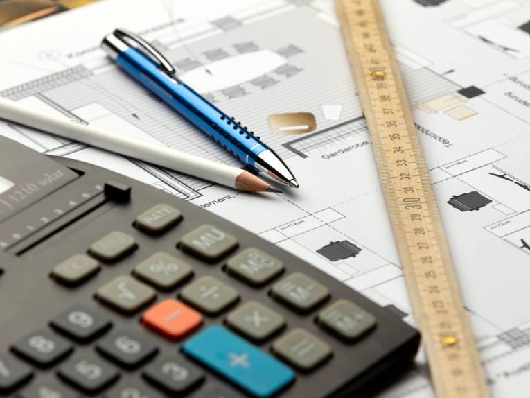 Auf dem Grundriss eines Gebäudes mit Wohn- oder Konferenzbereich liegen ein Taschenrechner, ein Lineal, ein Bleistift und ein Kugelschreiber.