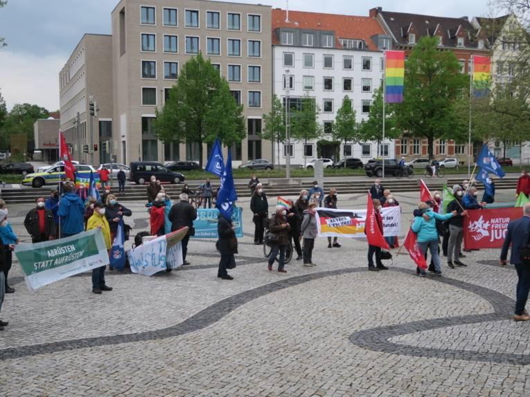 Menschen halten Flaggen und Banner vor dem Neuen Rathaus in Hannover