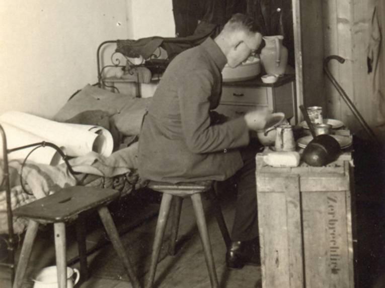 Mann essend auf einem Hocker vor einer Kiste sitzend, dahinter ein Bett, schwarz-weiß Aufnahme