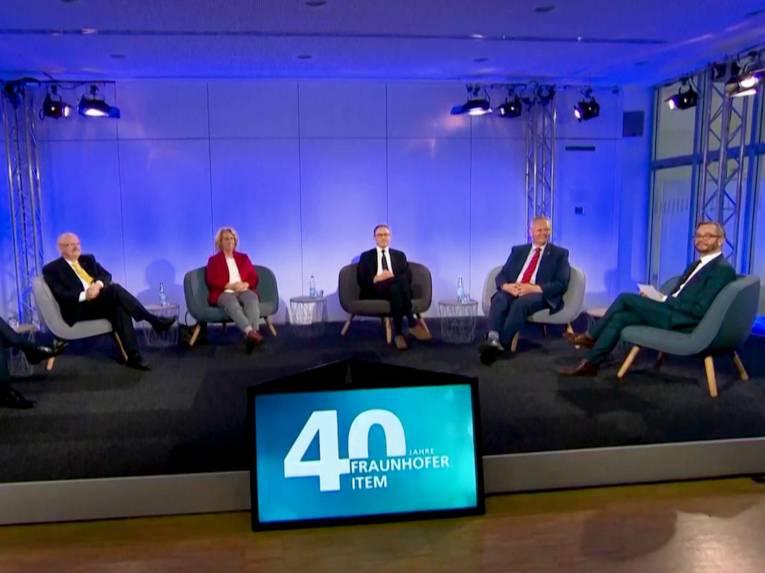 """Eine Frau und fünf Männer sitzen auf einem Podium, davor ein Bildschirm auf dem ein Logo, das den Schriftzug """"40 Jahre Fraunhofer ITEM"""" bildet, zu sehen ist."""