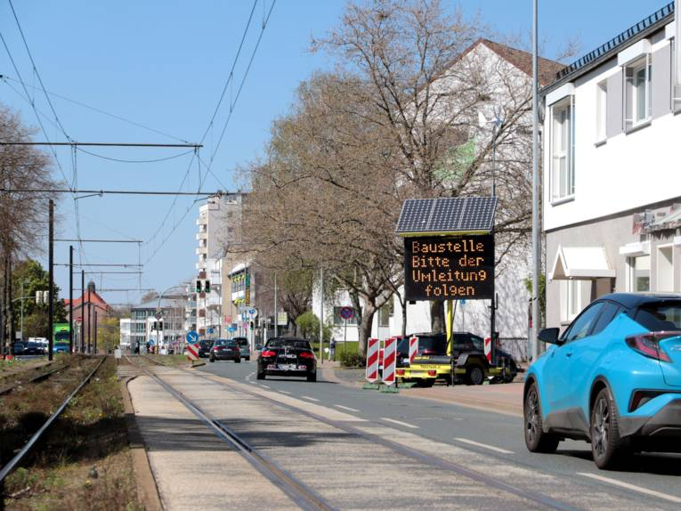 Eine zweispurige Straße mit Straßenbahnschienen im städtischen Bereich