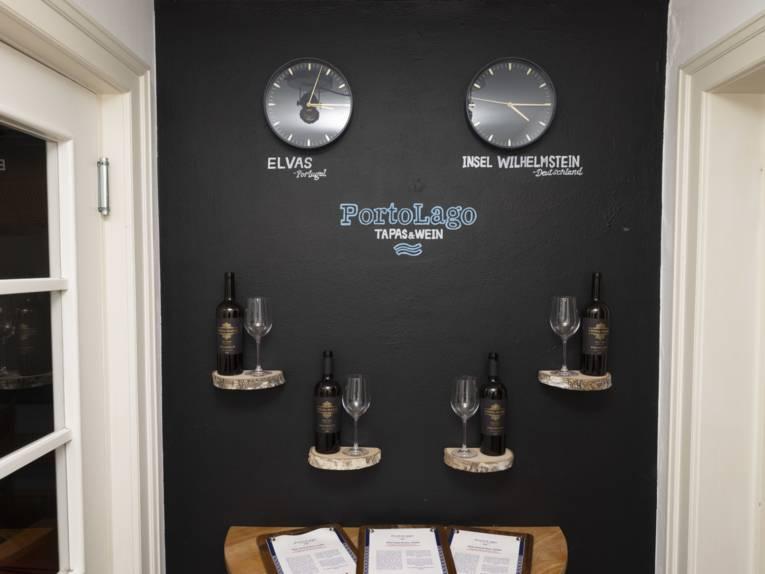 Dunkle Wand, zwei Uhren, die die Uhrzeit in Portugal und Deutschland anzeigen, Weine und Menükarte