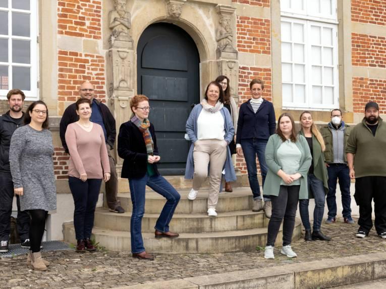 Acht Frauen und fünf Männer stehen auf den Stufen vor Schloss Landestrost.
