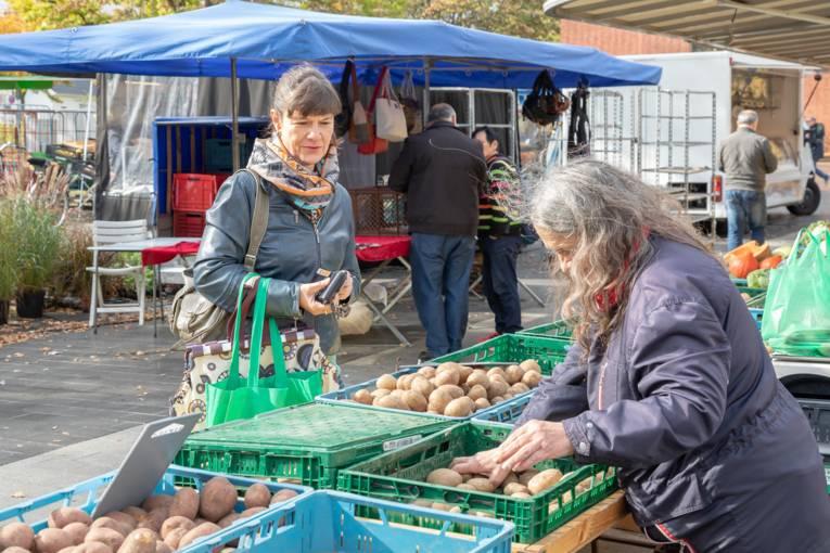 Eine Verkäuferin packt für ihre Kundin Kartoffeln ab.