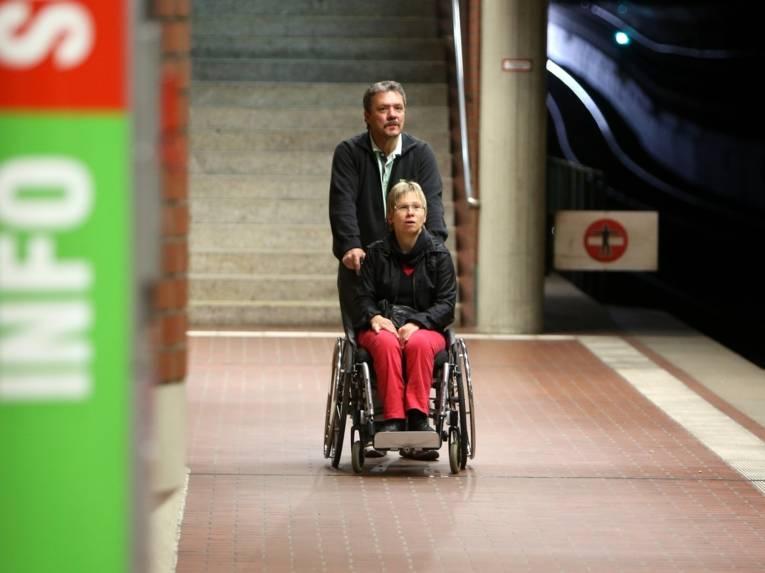 Der Fahrgastbegleiter begleitet die Rollstuhlfahrerin auf ihrer Fahrt mit der Stadtbahn.
