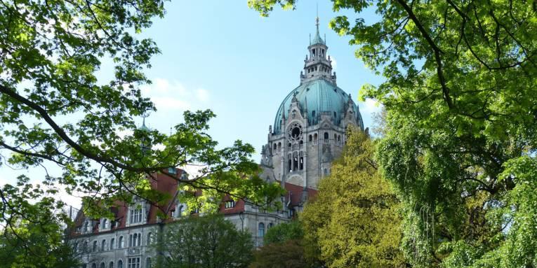 Das Neue Rathaus Hannover, eingerahmt von grünen Bäumen.