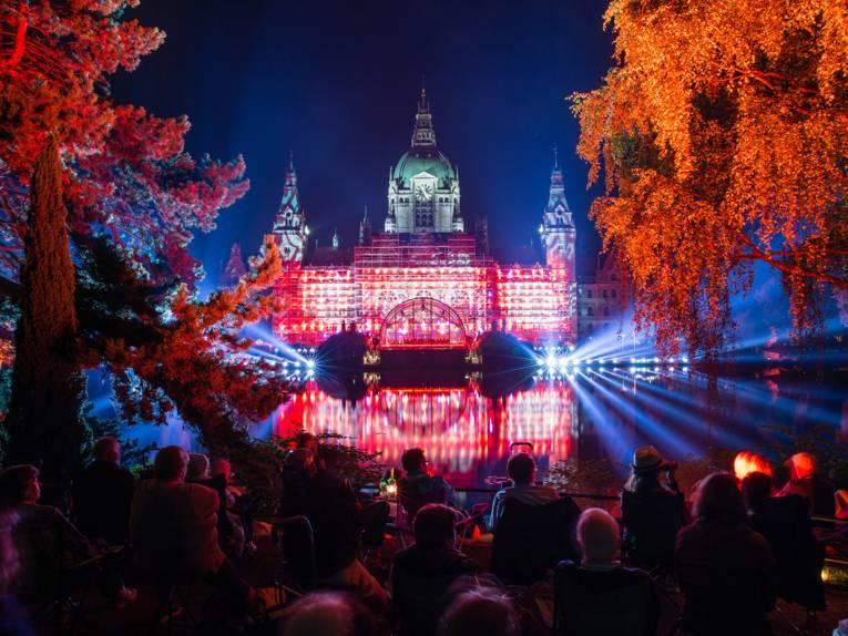 In der Ferne sitzen Menschen in einem Park und betrachten das festliche beleuchtete Neue Rathaus in Hannover bei Dunkelheit.