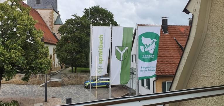 Die Friedensflagge der Mayors for Peace ergänzt das Gemeindewappen und Logo von Spraitbach