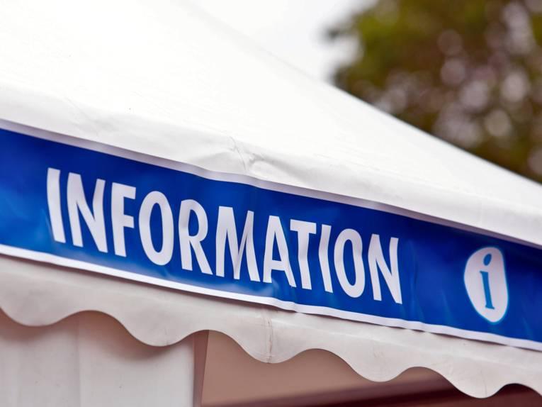 """Am Dach eines weißen Zeltes ist ein Banner angebracht. Darauf steht """"Information"""", daneben ist das """"i"""" für Information."""