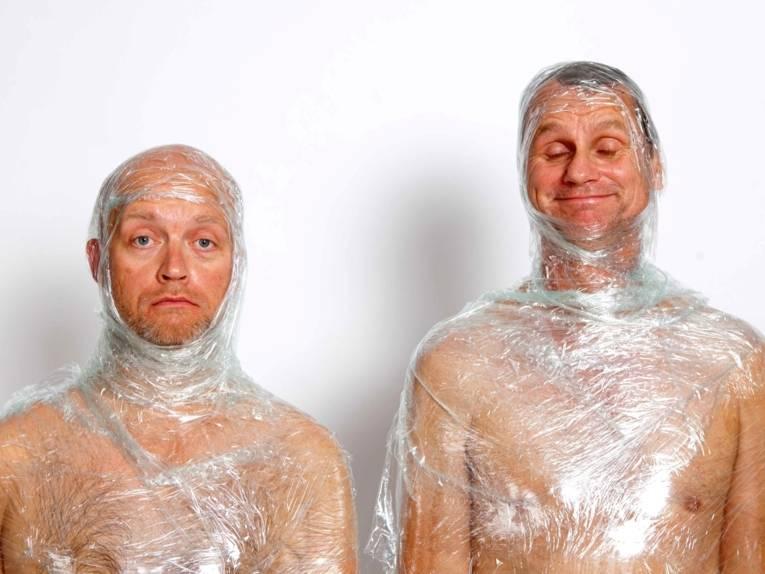 Zwei nackte Männer, ihre Köpfe und Oberkörper sind in Klarsichtfolie eingewickelt.
