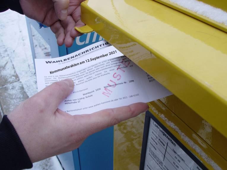 Eine Wahlbenachrichtigungskarte für die Landtagswahl 2013 wird in einen Briefkasten geworfen