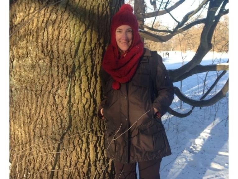 Eine Person mit Jacke, Schal und Müttze lehnt an einem Baum in winterlicher Umgebung.