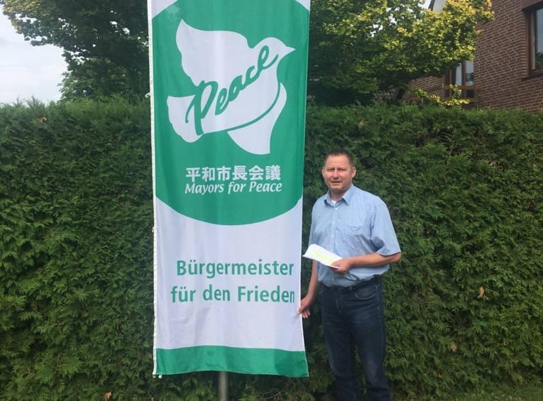 Bürgermeister Clemens Leder hisst die Mayors for Peace Flagge in Wendisch-Evern