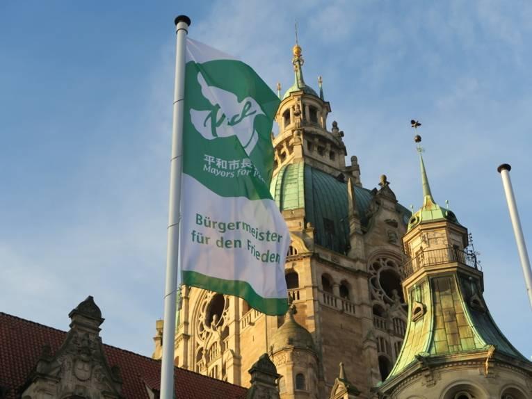 """Die Flagge der """"Mayors for Peace"""" weht im Wind, vor dem Neuen Rathaus in Hannover."""