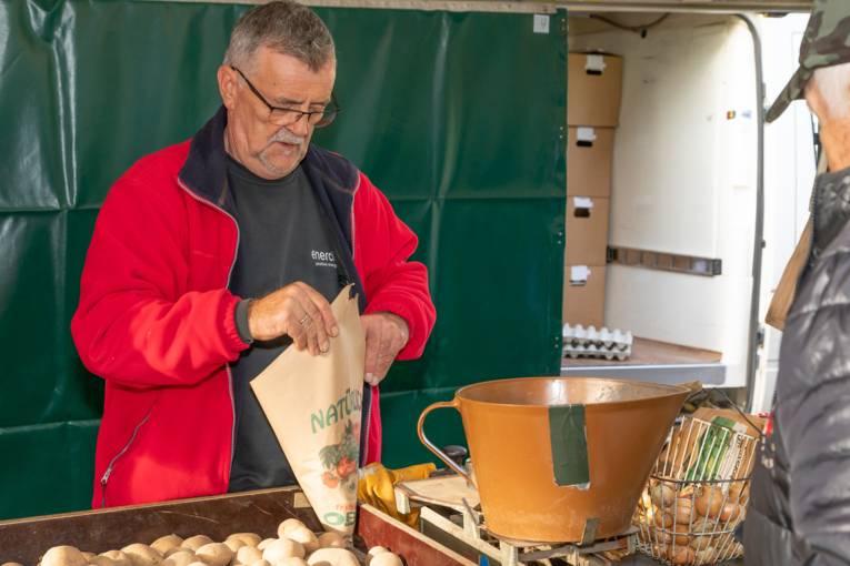 Ein Händler tütet Kartoffeln für einen Kunden ein.