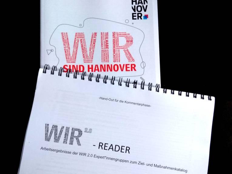 """Ein Reader mit der Aufschrifft """"WIR 2.0-Reader. Arbeitsergebnisse der WIR 2.0-Expert*innengruppen zum Ziel- und Maßnahmenkatalog"""". Darunter sieht man den oberen Teil des Strategiepapiers mit der Aufschrift """"WIR sind Hannover""""."""