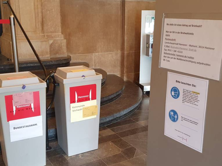 Ein Hinweisschild zu Briefwahlen und zwei Wahlurnen im Eingang des Neuen Rathauses