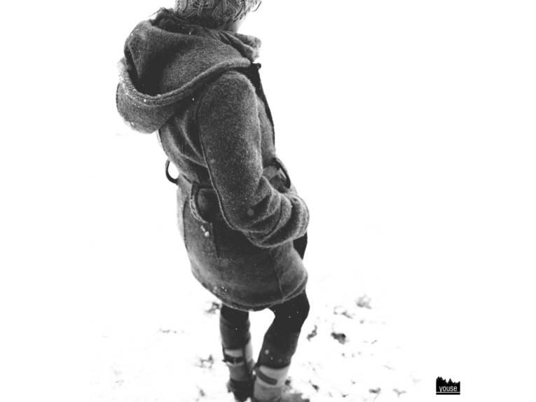Schwarz-Weiß-Foto einer Person in einem Wollwalkmantel im Schnee.