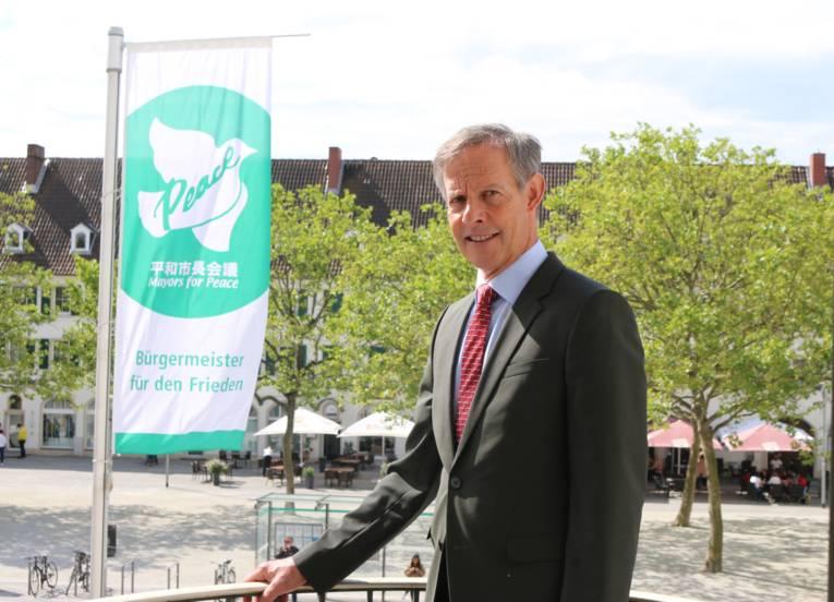 Oberbürgermeister Udo Bausch vor der Flagge der Mayors for Peace