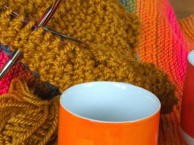 Wolle, Stricknadeln, etwas Gestricktes und Tassen sind auf einem Tisch.