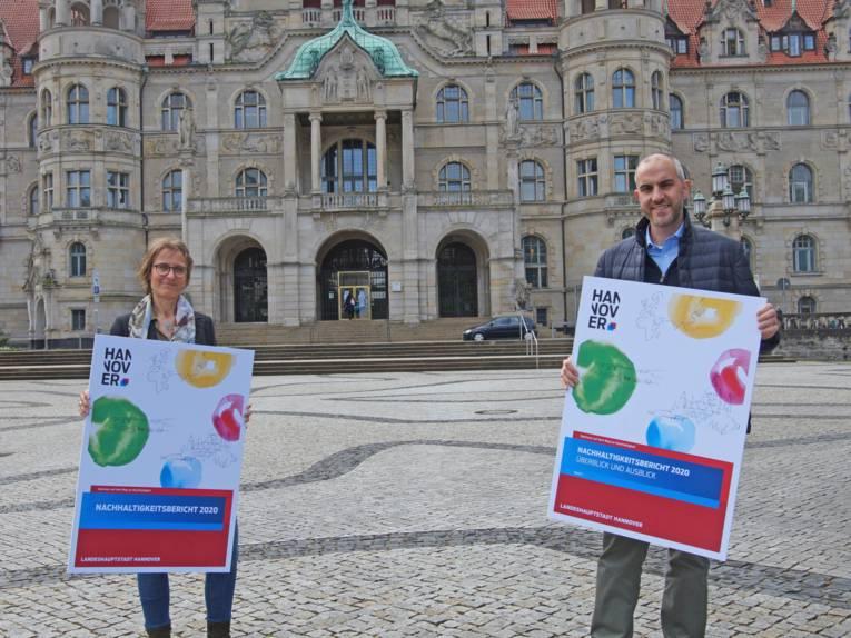 Zwei Personen mit Plakaten vor eine, Gebäude.