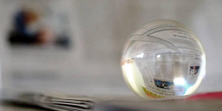 Eine Glaskugel liegt auf einem Stapel Zeitungen, im Hintergrund ist auch eine Zeitung aufgeschlagen. In der Glaskugel sind Teile der Zeitungen zu erkennen.