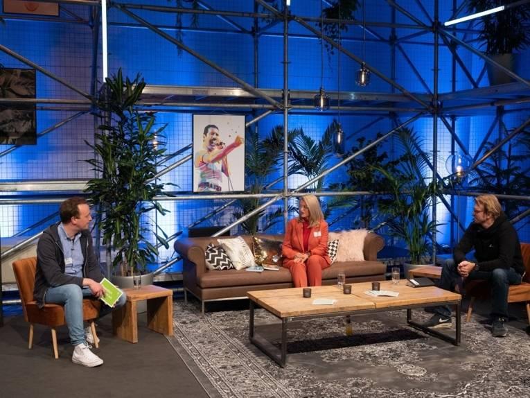 Zwei Männer und eine Frau auf Sesseln und einem Sofa sitzend.