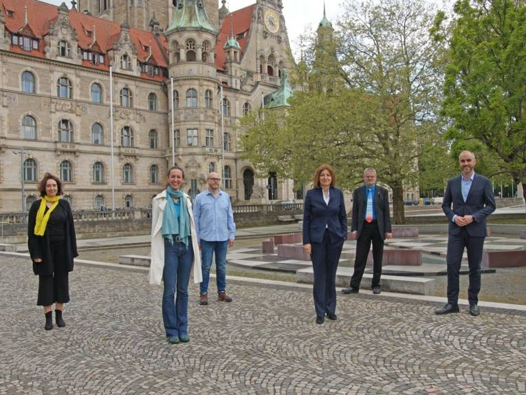 Drei Frauen und drei Männer vor dem Neuen Rathaus.