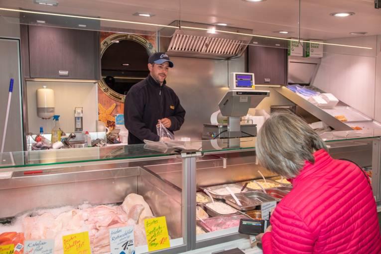 Frische Fischfilets in einem Marktwagen; eine Kundin kauft Waren.