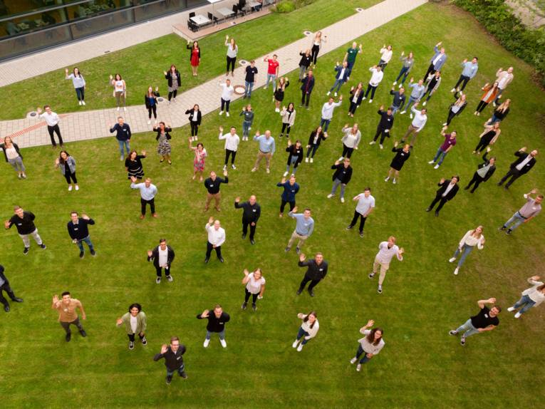 Viele Menschen auf einem grünen Rasen die winken. Sie sind von oben herab fotografiert.