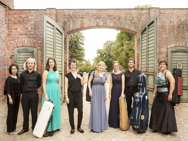Sechs Frauen und zwei Männer, teils mit Instrumentenkoffern.