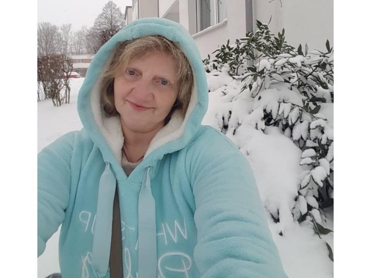 Eine Frau in einem dicken Fleecepulli mit Kapuze in winterlicher Umgebung.