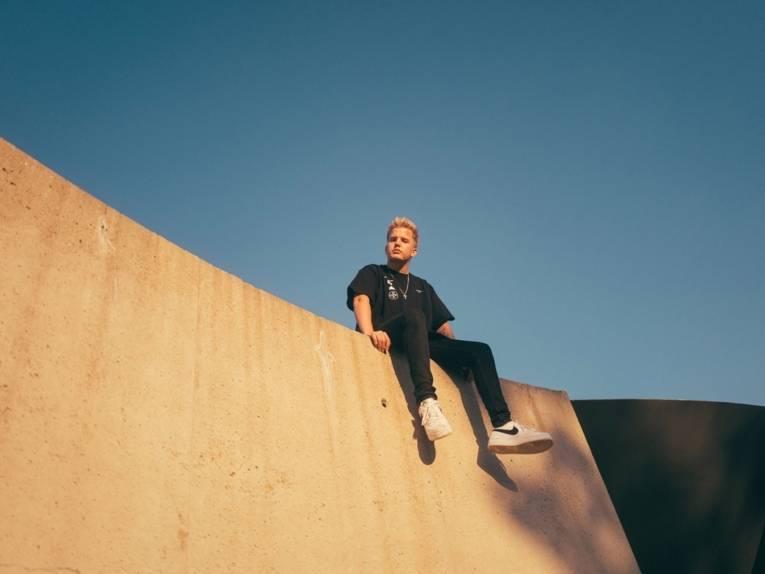 Ein blonder junger Mann sitzt auf einer Art Mauer und schaut von oben in die Kamera.