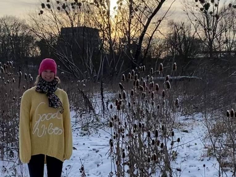 Eine Frau im gelben Strickpulli in einer winterlichen Umgebung